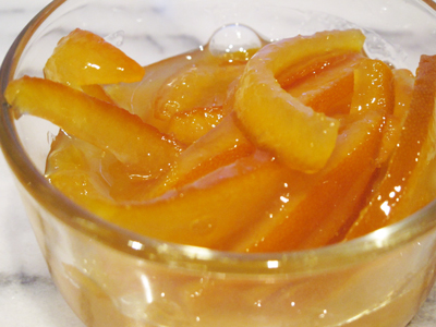 Orange confit is, basically, candied orange peel in the sugar syrup it was cooked in.