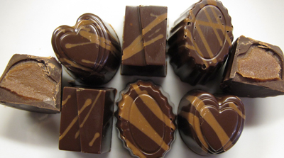 My latest molded-chocolate practice session was fraught with problems, but the two-toned shell seemed to work out OK. Here, a milk-chocolate ganache was piped into a bittersweet chocolate shell with milk-chocolate striping. (Click on image to see larger photo.)